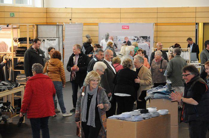 Das Bild zeigt eine Halle mit vielen Menschen und verschieden Ständen mit Kleidung.