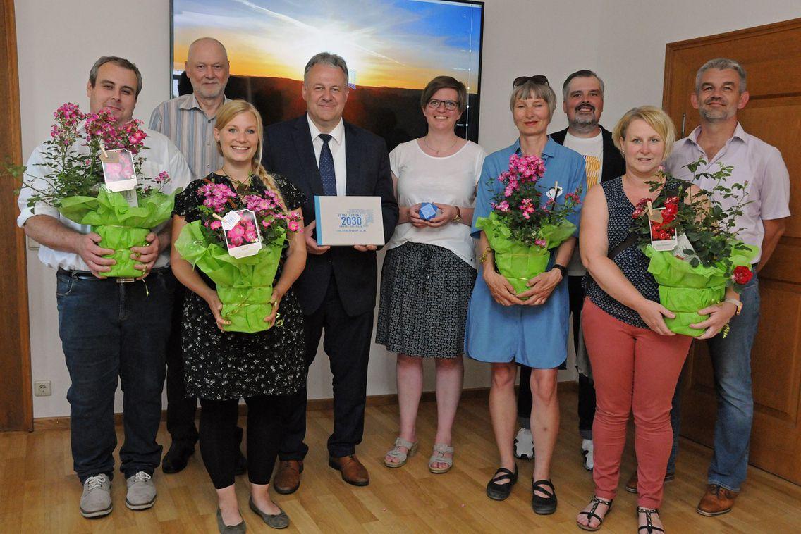 Neun Personen stehen vor einem Bild mit Sonnenuntergang und feiern die Verabschiedung des Leitbildes 2030. Eine Person hält das Leitbild in die Kamera, vier weitere halten Blumen in den Händen.
