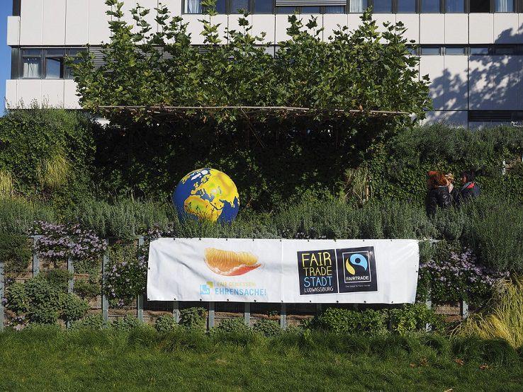 Eine Erdkugel im Garten vor einem grauen Gebäude und einem Plakat der Fairtrade Stadt Ludwigsburg