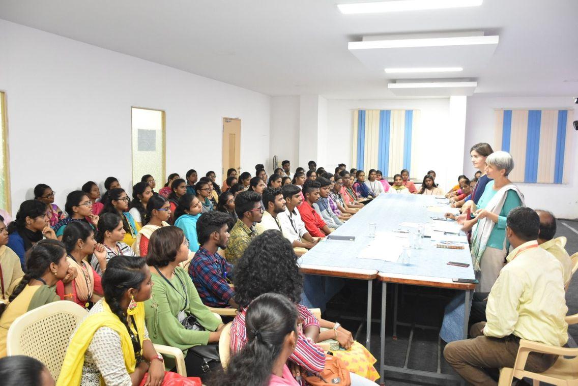 Das Bild zeigt eine Versammlung mit vielen Menschen, die etwas besprechen.