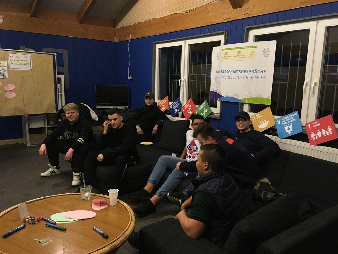"""Eine Gruppe Jugendlicher sitzt oder liegt auf Sofas und unterhält sich. Im Hintergrund ist ein Plakat mit dem Schriftzug """"Nachbarschaftsgespräche, Zusammenleben - Aber wie?"""" zusammen mit einigen bunten Plakaten der SDGs zu sehen"""