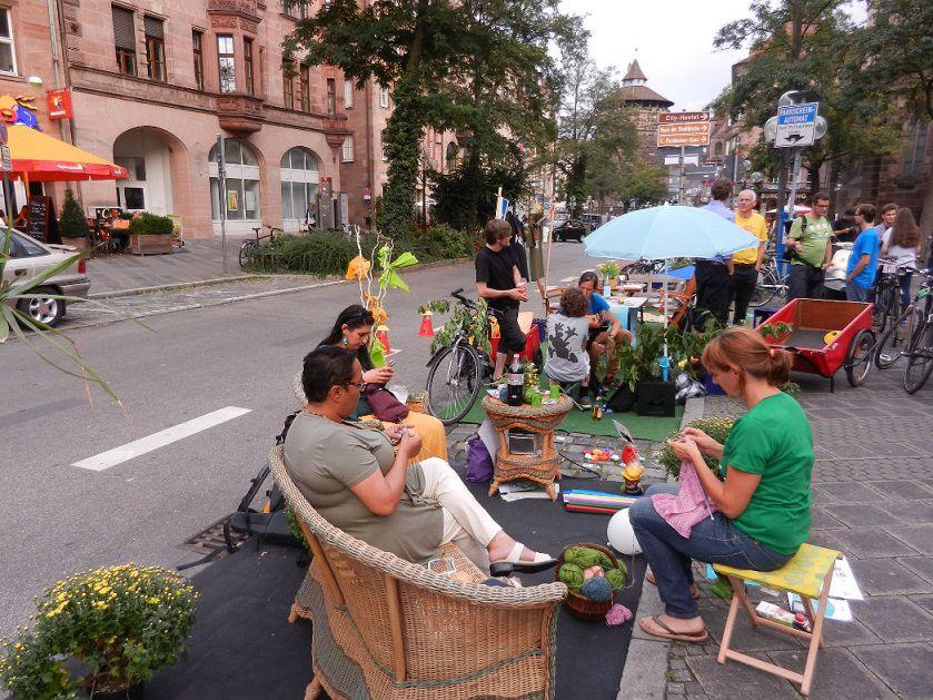 Mehrere Personen sitzen auf Stühlen und Sesseln am Straßenrand und basteln während des Parking Days in Nürnberg