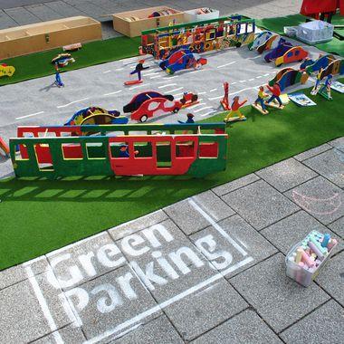 """Eine Spielmatte mit Straßen und Grünstreifen auf der Verkehr simuliert werden kann mit bunt bemalten Autos, Bussen und Fußgängern aus Holz. NEben einem Eimer Kreide steht der Slogan """"Green Parking Day""""."""