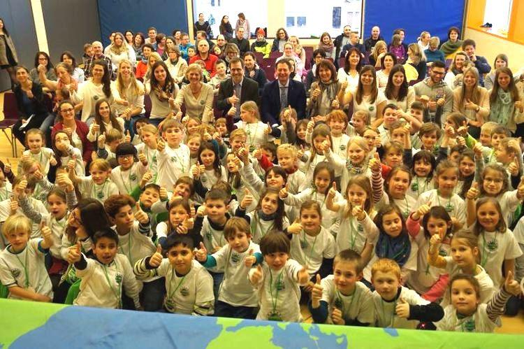 Eine große Gruppe von Kindern und Erwachsene stehen vor einer Bühne auf der Umrisse eines Globus zu sehen sind und strecken einen gehobenen Daumen in die Luft