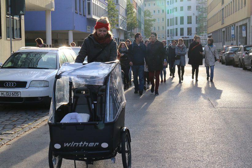 """Im Vordergrund fährt ein Lastenfahrrad am Rand einer Straße in München. Im Hintergrund folgen ca. 15 Personen im Rahmen des Spaziergangs von """"Orte des Wandels"""""""