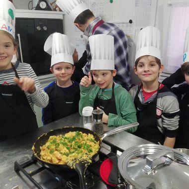 Kinder präsentieren stolz und glücklich ihr selbstgekochtes Essen.