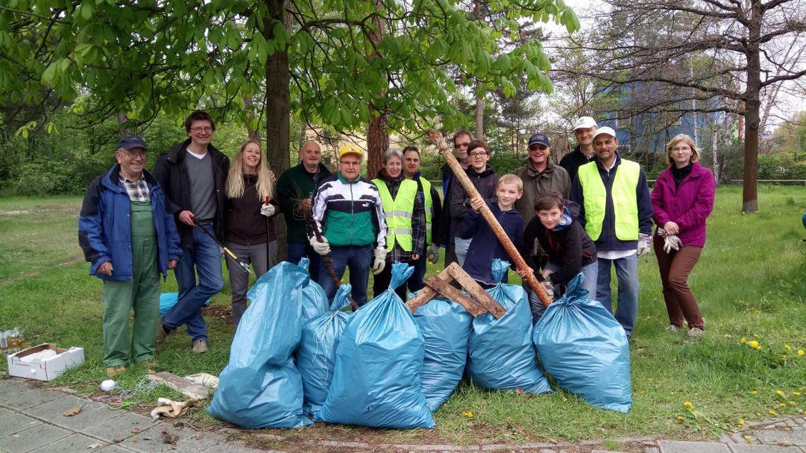 Eine Gruppe von Menschen steht am Rand einer Wiese und präsentiert mehrere Müllsäcke mit gesammeltem Plastikmüll