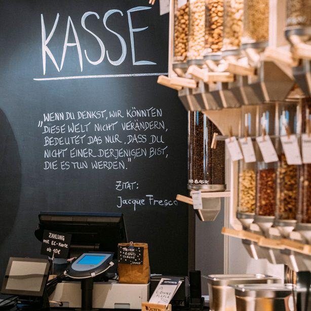 Das Bild zeigt die Kasse des Unverpackt-Ladens sowie eine Reihe von mit Lebensmitteln gefüllten Gläsern.