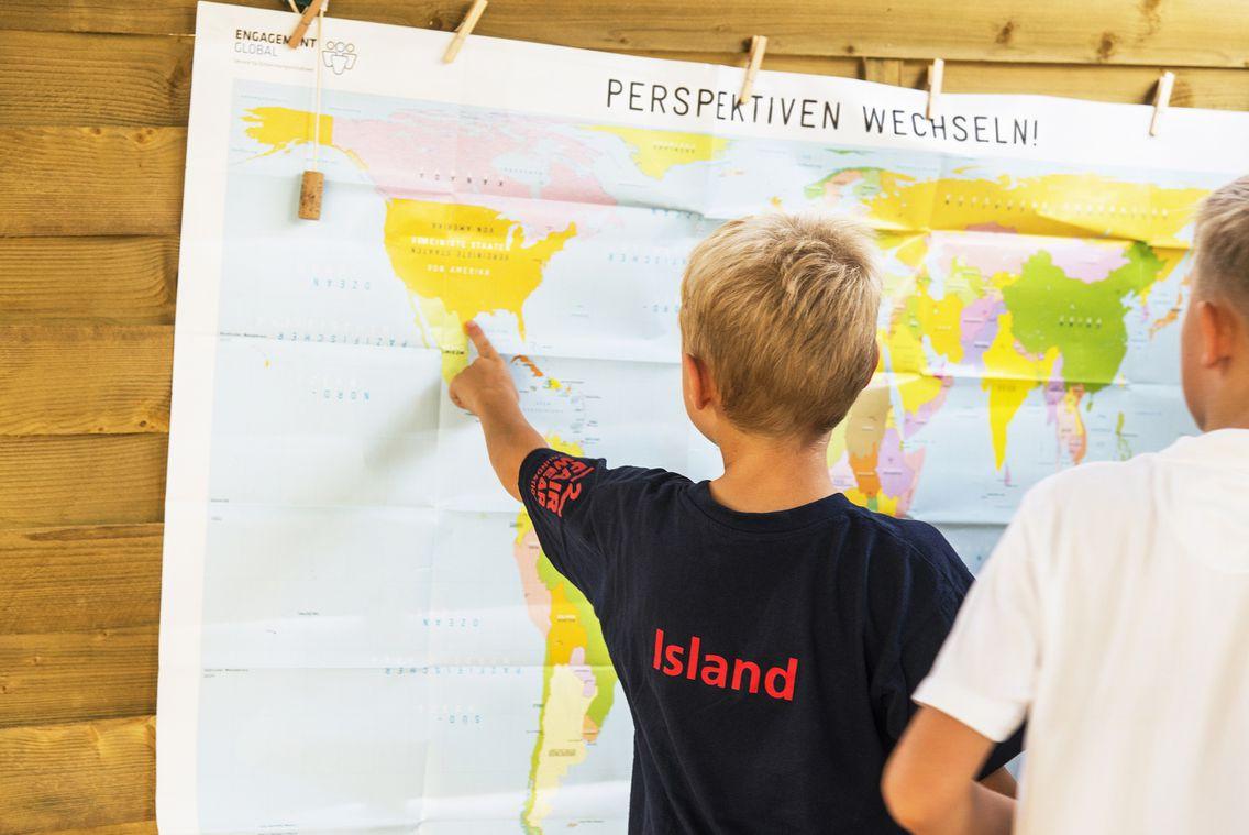 zwei Jungen stehen vor einer Weltkarte. Ein Junge, der ein schwarzes T-Shirt mit der Aufschrift Island trägt, deutet auf den Kontinent Nordamerika.