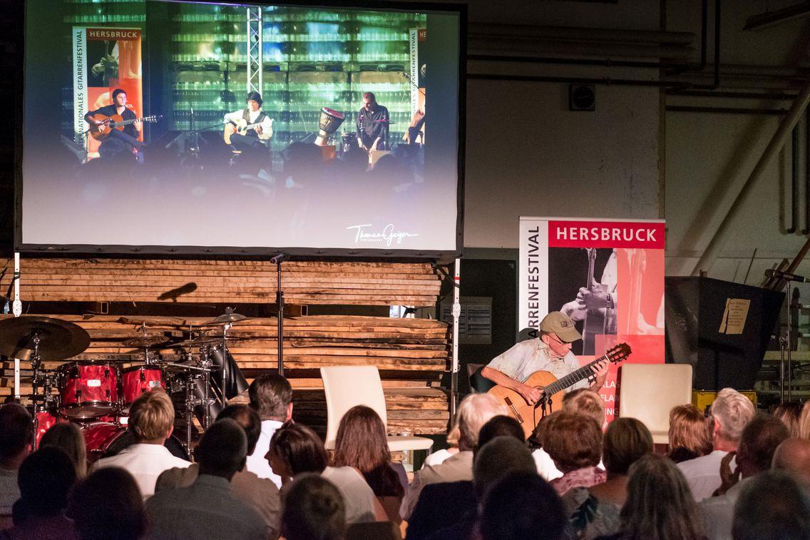 Ein Musiker gibt auf einer kleinen Bühne ein Konzert. Im Hintergrund der Bühne sind ein Schlagzeug sowie eine Leinwand mit einem weiteren Konzert zu sehen. Im Vordergrund sitzen die Zuschauer dicht bei der Bühne