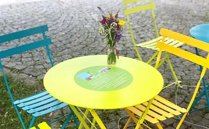 Ein strahlend gelber Cafétisch mit einem gelben und einem hellblauen Stuhl. Auf dem Tisch steht ein blumenstrauß