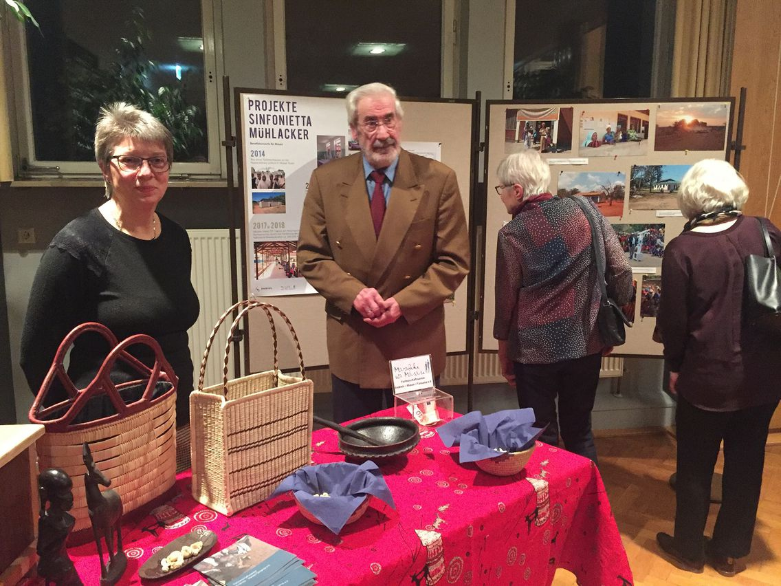 Zwei Personen betreuen einen Stand der AG Tansania. Im Hintergrund betrachten zwei Besucherinnen eine Fotostrecke aus Tansania. Auf dem Tisch sind u.a. Taschen als Fairtradeprodukte angeboten