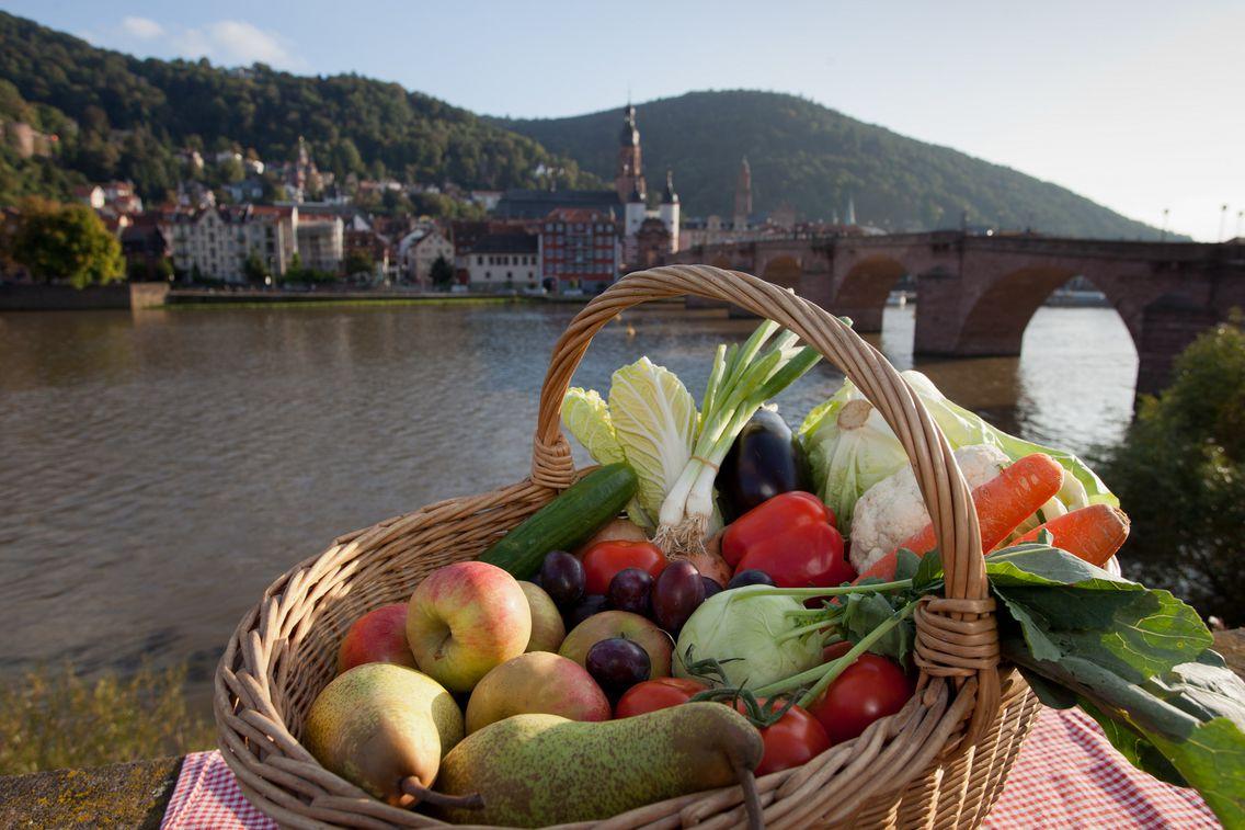 Korb gefüllt mit Obst und Gemüse vor der Stadtkulisse von Heidelberg