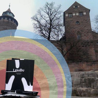 Das Leihbu umgeben von Regenbogenfarben. Im Hintergrund die Nürnberger Burg.