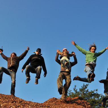 Sieben Mitglieder von Wirundjetzt e.V. springen gemeinsam für das Foto von einem Haufen Holzschnitzel herunter.