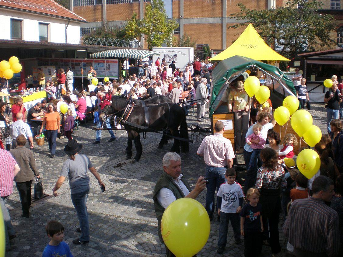 Viele Menschen stehen auf einem Platz. Es sind viele Stände zu sehen und eine Kutsche gezogen von zwei schwarzen Pferden. Viele gelbe Luftballons sind auf dem gesamten Platz aufgehängt.