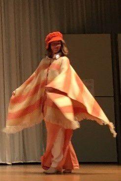 Eine weitere Person führt bei der Modenschau ihre Kleidung vor.