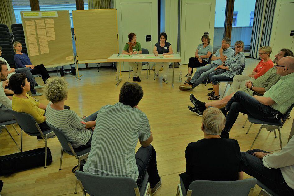 Mehrere Personen diskutieren in einem Stuhlkreis. Die Ergebnisse werden direkt an einer nebenstehenden Pinnwand festgehalten.