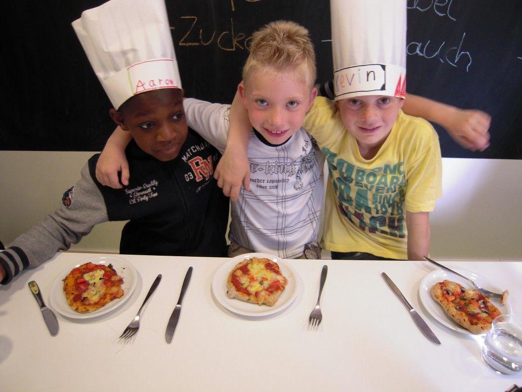 Kinder von Slow Food Karlsruhe glücklich mit Ihrer selbstgebackenen Pizza.