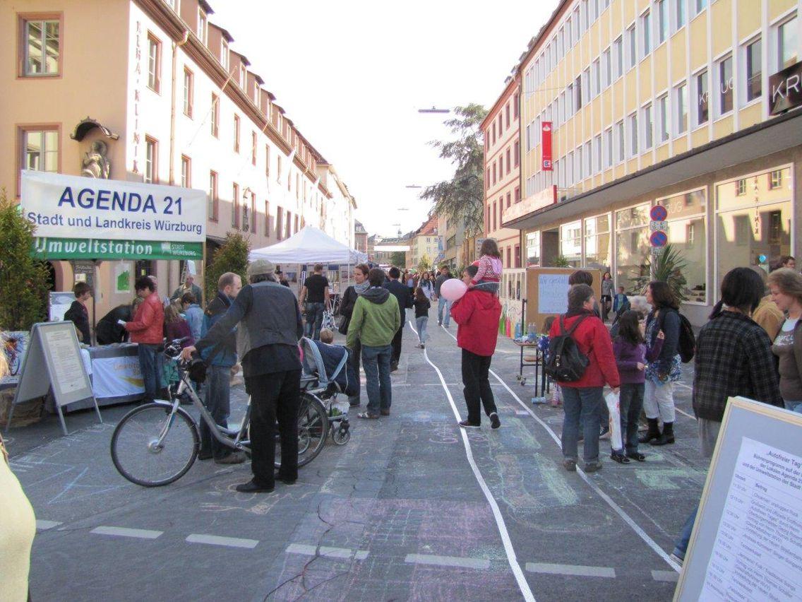 Mehrere Menschen stehen auf einer Straße sowie einem Stand der Würzburger Agenda 21, eine Person mit Fahrrad, ein Kind wird auf den Schultern getragen