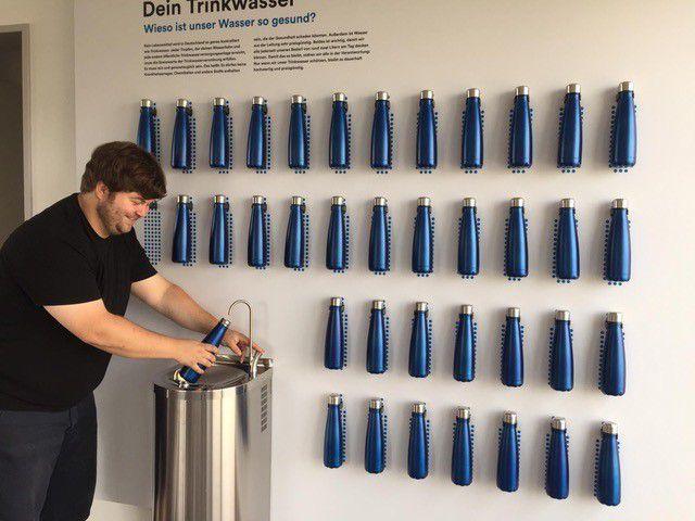 Ein Mann zapft Wasser an einem Indoor-Trinkbrunnen. An der Wand hängen viele Wasserflaschen zum Befüllen.