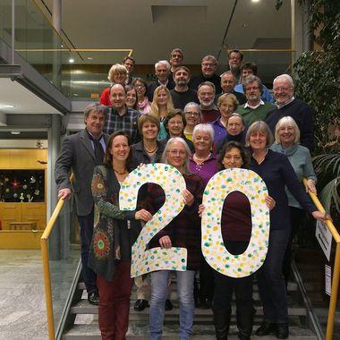 Beteiligte der Agenda 21 im Landkreis Fürstenfeldbruck stehen auf einer Treppe und halten in großen Lettern die Zahl 20 hoch zur Feier des 20-jährigen Jubiläums.