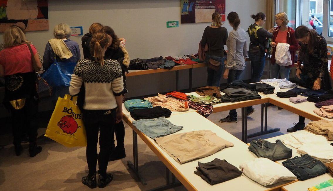 Das Bild zeigt Tische mit Kleidungsstücken und Menschen drumherum.