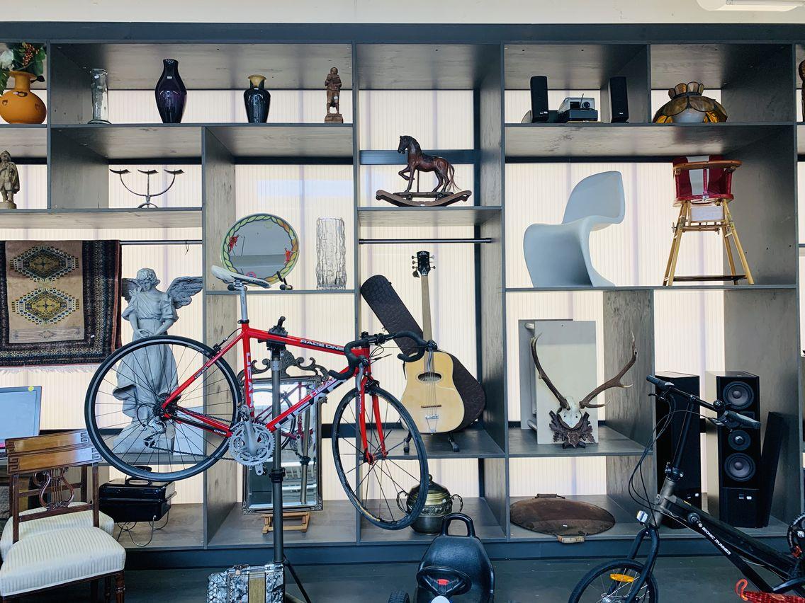 Verschiedene Gegenstände stehen in einem Regal vor einer beleuchteten Wand, u.a. zwei Fahrräder, eine Gitarre, mehrere Vasen und ein Kinderstuhl.