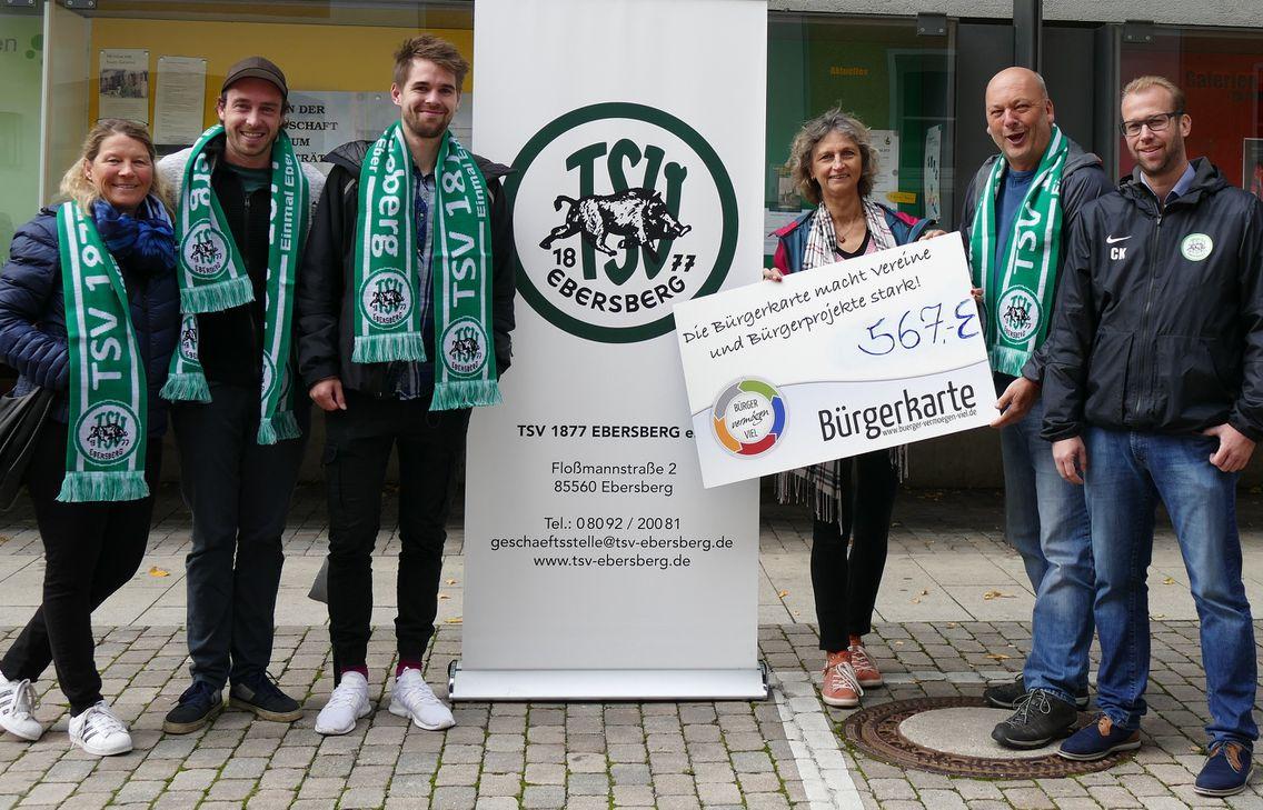 Fußballer posieren mit einer großen Bürgerkarte.