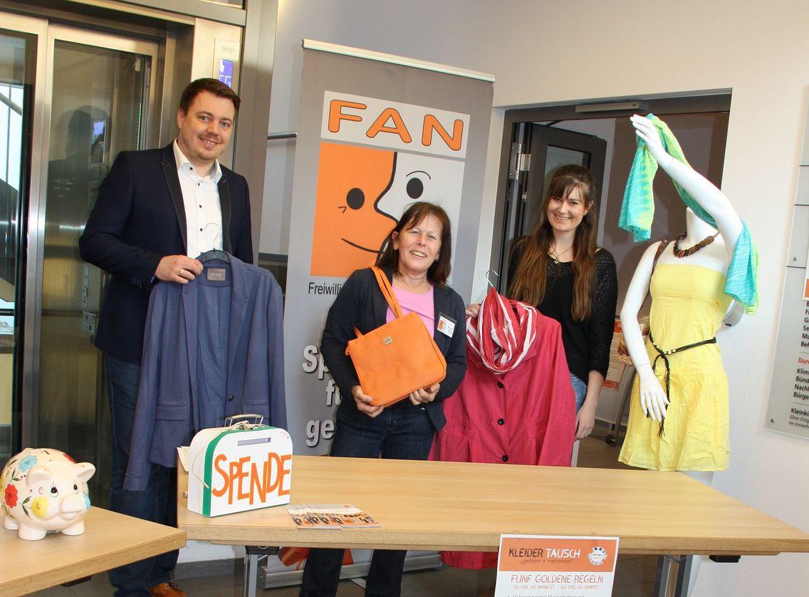 Das Bild zeigt engagierte Menschen mit Kleidungsstücken in der Hand hinter einen Tisch mit Banner des Vereins.