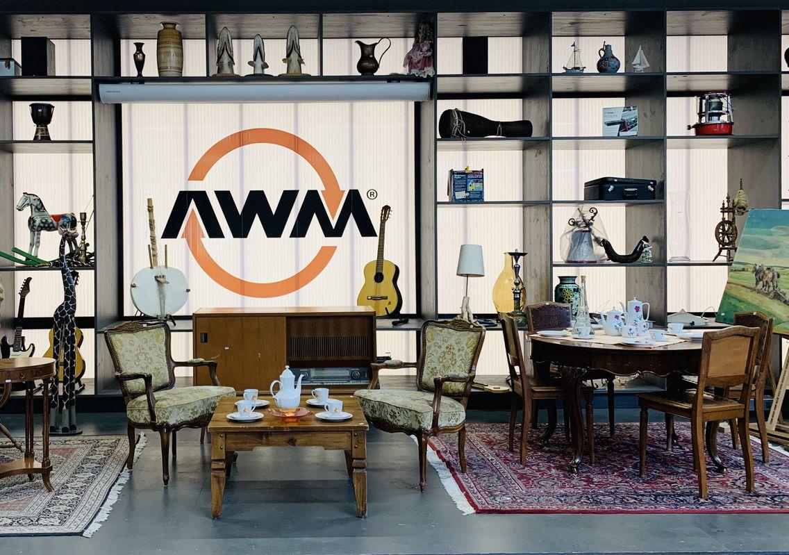 """Vor einer beleuchteten Wand mit dem Logo """"AWM"""" der Abfallwirtschaftsbetriebe München stehen Kaffeetische mit Stühlen in klassischem Stil mit gedeckten Teeservice. Im Regal stehen verschiedene Gegenstände wie Vasen, eine Gitarre oder Lampen."""