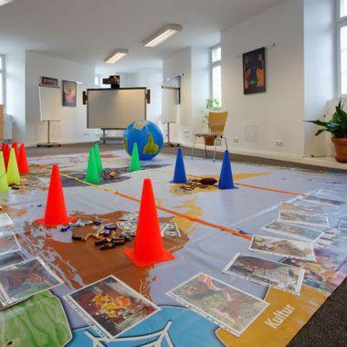 Abgebildet ist ein Seminarraum, indem eine Weltkarte am bodend liegt mit einigen Bildern und Hütchen. Hier sollen Themen der Nachhaltigkeit spielend angegangen und diskutiert werden.