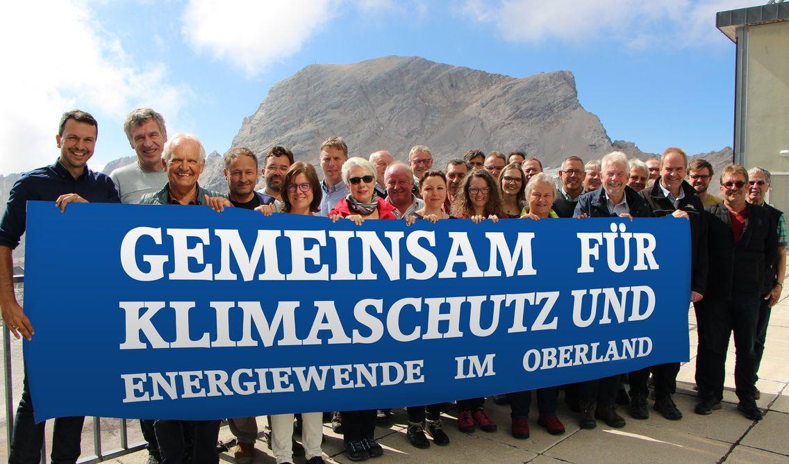 """Gemeinsam für Energiewende und Klimaschutz im Oberland"""". Im Hintergrund ein Berggipfel."""