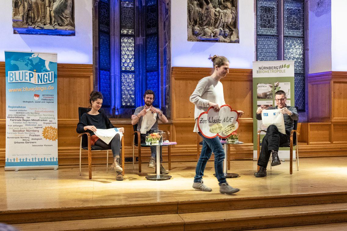 Vier Leute beim Zero Waste Workshop stehen bzw. sitzen auf einer Bühne. Links von Ihnen das Plue Pingu Banner.