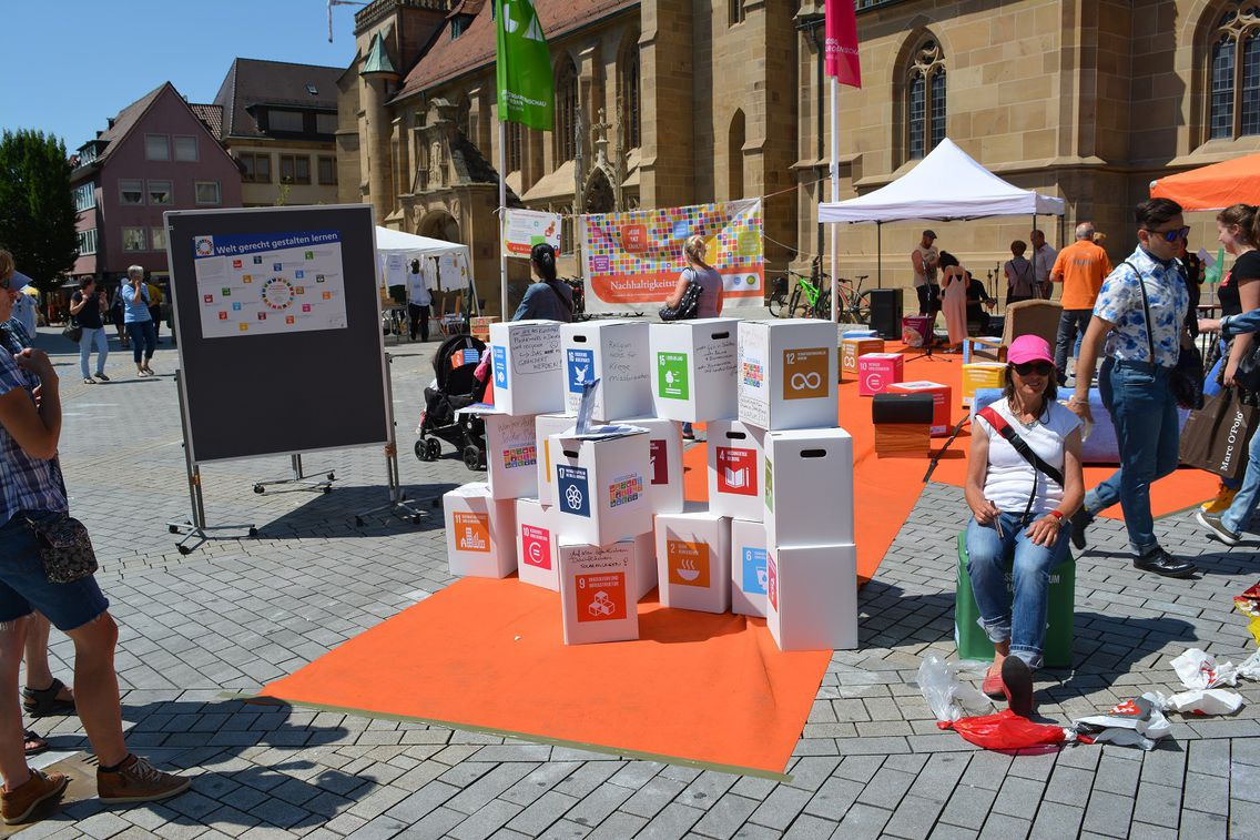 Auf einem gepflasterten Platz stehen mehrere Kartons, welche mit Zielen der Sustainable Development Goals beschriftet sind, auf einem orangenen Teppich. Im Hintergrund sind Schautafeln sowie Pavillons der Lokalen Agenda Heilbronn zu erkennen. Im Vordergrund stehen mehrere Leute interessiert vor der Kulisse.