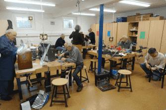Viele Menschen reparieren im Raum der Initiative verschiedenste Gegenstände.