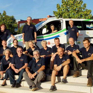 Das Team der Bürgerinitiative sitzt auf Treppen. Im Hintergrund ist der Bürgerbus zu sehen.
