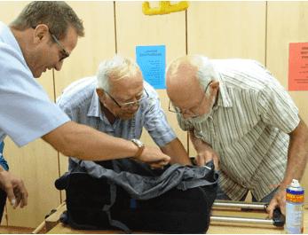 Drei Herren bei der Reperatur einer Tasche.