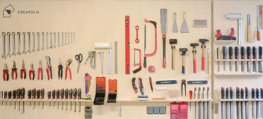 An einer Wand hängt geordnet eine Vielzahl an Werkzeugen an verschiedenen Leisten. Oben links ist das Logo des Creapolis Coburg zu sehen.