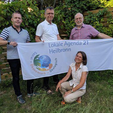 Vier Personen, die das Sprechteam der Lokalen Agenda 21 bilden, stehen vor einem grün bewachsenen Holzzaun und halten das Banner der Lokalen Agenda in ihren Händen.