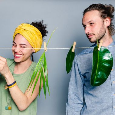 Es sind zwei Personen zu sehen, die mit Klammern verschiedene Arten von Blättern an einer Wäscheleine befestigen.