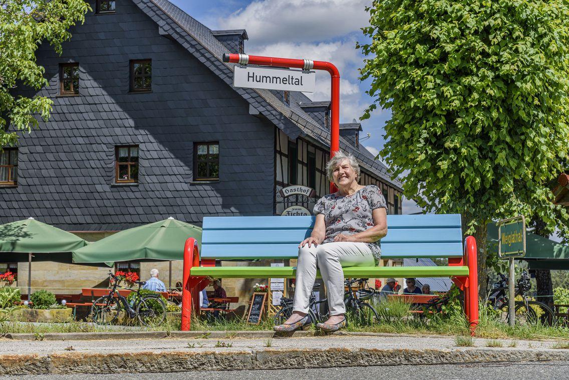 Eine Frau sitzt auf einer Mitfahrerbank.