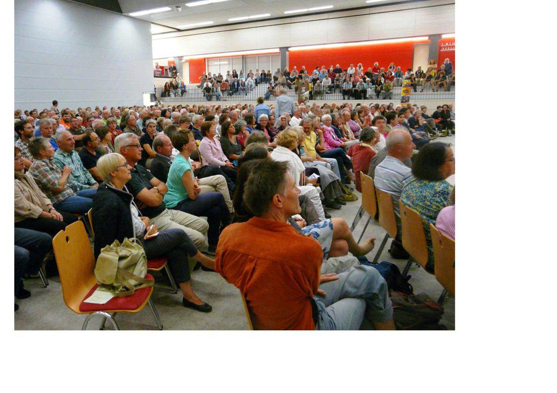Die Murger Bürger*innen sitzen aufgereiht in einem großen Veranstaltungsort. Möglicherweise verfolgen sie gerade einem Vortrag oder nehmen an einer Diskussionsrunde teil.