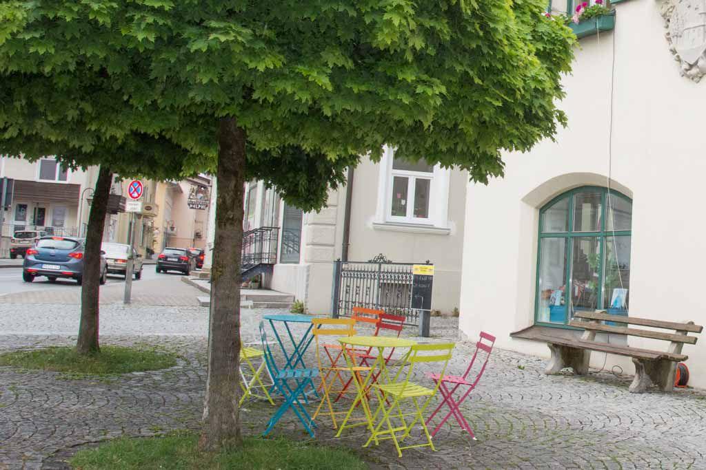 Unter zwei Bäumen auf einem geplasterten Platz stehen viele bunte Café-Tische und Stühle. Im Hintergrund ist ein Schaufenster sowie eine Straße mit Autos zu sehen