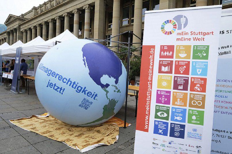 Zu erkennen ist ein Informationsstand mit den 17 SDGs der Nachhaltigkeit auf einem Roll-up und einer Weltkugel nebenan.