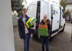Zwei Mitglieder*innen der albTech eSG liefern an Weihnachten Geschenke aus.