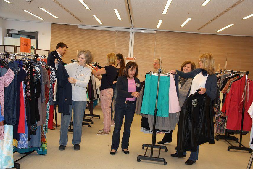 Das Bild zeigt Kleiderständer und Menschen die sich diese ansehen.