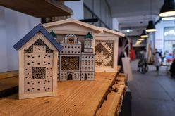 Einige fertige Vogelfutterhäuser stehen nebeneinander. Eines davon stellt das Augsburger Rathaus dar.