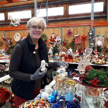 Eine Frau dekoriert Weihnachtsdeko für den Verkauf auf dem Flohmarkt.