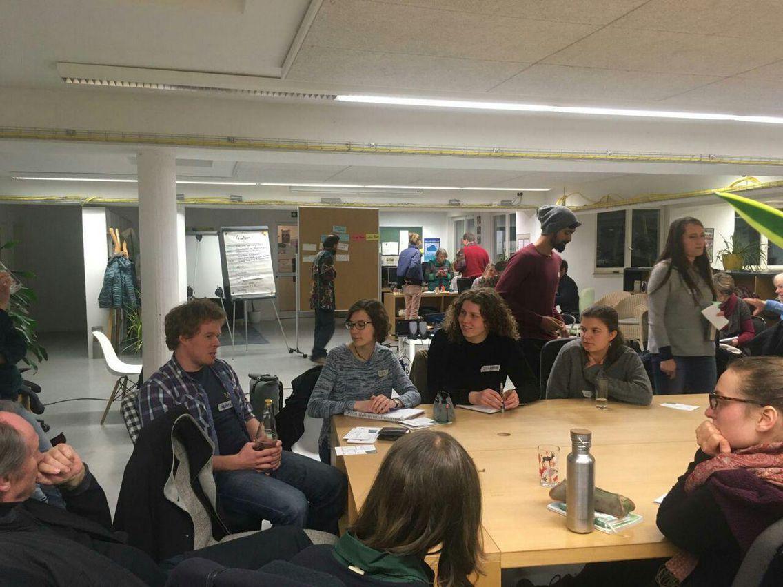 Mehrere Personen diskutieren an einem langen Tisch. Im Hintergrund sind weitere Personen zu sehen, die teilweise ebenfalls an einem Tisch stehen oder vor Moderationswänden stehen.